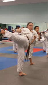 Brown Belt Meghan performs a side kick life stretch